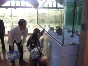 水槽の魚を見る親子